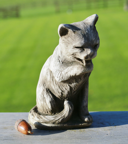 Miniature licking cat garden ornament made from hardwearing reconstituted stone